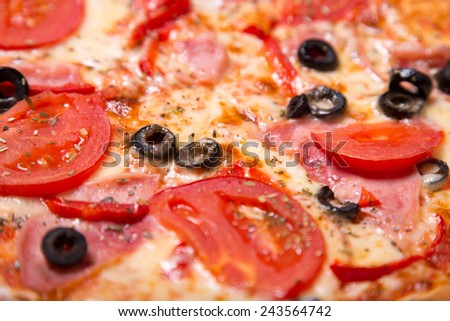 Close-up shot of tasty Italian pizza with ham, tomatoes and olives, selective focus   - stock photo
