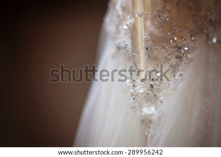 Close up shot of the rear side of a wedding dress with lace and crystals with a plain brown background and shallow depth of field. Vintage colour/color effect.
