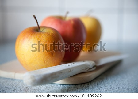 Close up shot of three apples and an used/older knife