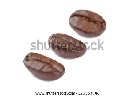 Close-up shot of three coffee beans on white background.