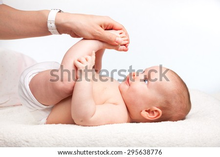 Close-up shot of three month baby girl receiving leg massage from a female massage therapist - stock photo
