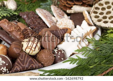 Close up shot of traditional German christmas cookies, such as Aachener Printen, Marzipankartoffeln, Zimtsterne and iced gingerbread, decorated with chocolate truffles, pieces of wood and greenery. - stock photo