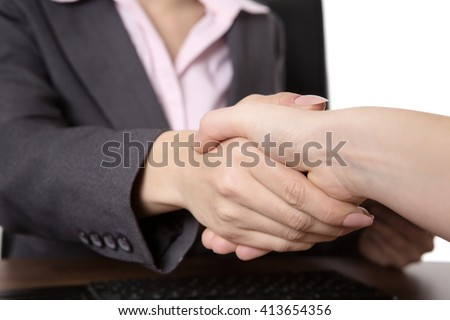 close up shot of two business women shaking hands.