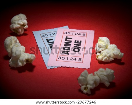 Close up shot of two generic admission tickets and some popcorns arround. - stock photo
