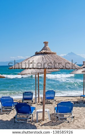 Close up shot of umbrella on the sandy beach with sea waves and sky in the background - stock photo