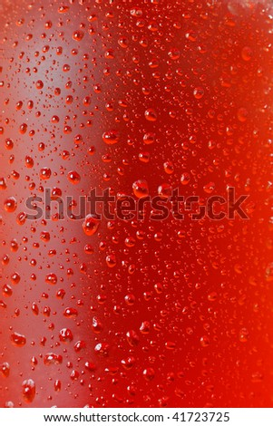 Close up shot of water drops on glass bottle in red color