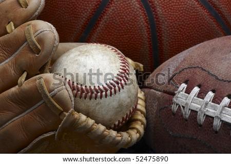 close up shot of well worn baseball in baseball glove, football and basketball - stock photo