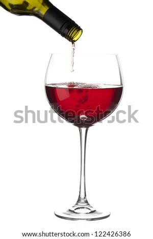 Close-up shot of wine bottle pouring red wine in wine glass against white background. - stock photo