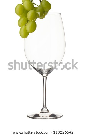 Close-up shot of wine glass with grapes on white background - stock photo