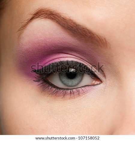 Close-up shot of woman eye with color makeup looking at camera - stock photo