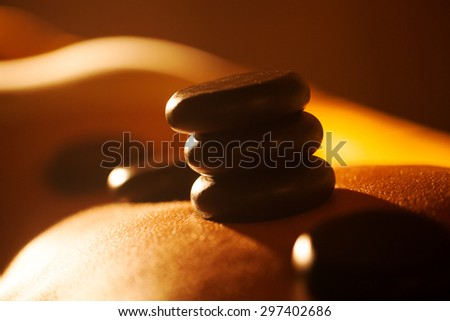 Close-up shot of woman receiving hot stone massage at beauty spa. Black rocks on the skin shining in sunlight - stock photo