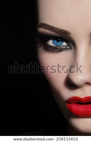 Close-up shot of woman's face with red lips and smoky eyes, selective focus - stock photo