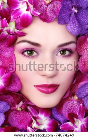 Close-up shot of young beautiful woman face with bright orchids around - stock photo
