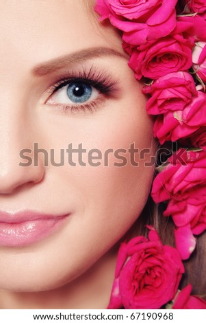 Close-up shot of young beautiful woman face with pink roses in hair - stock photo