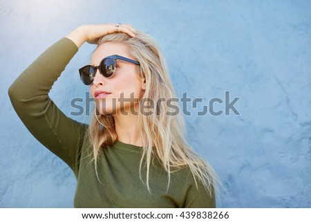 Close up shot of young blonde in sunglasses looking away with her hand in hair. Caucasian female model over blue wall. - stock photo