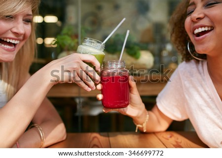 Close up shot of young friends toasting drinks at sidewalk cafe. Two happy women enjoying drinks and chat at outdoor coffee shop. - stock photo