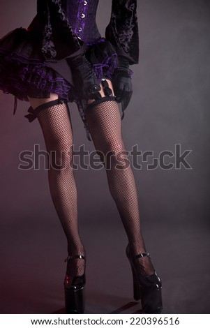 Close-up shot of young woman putting on stockings, studio shot on smoky background  - stock photo