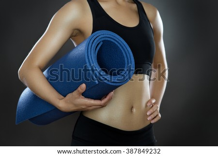 close up shot with low key lighting of a woman's midriff holding a sports mat shot in the studio on a gray background