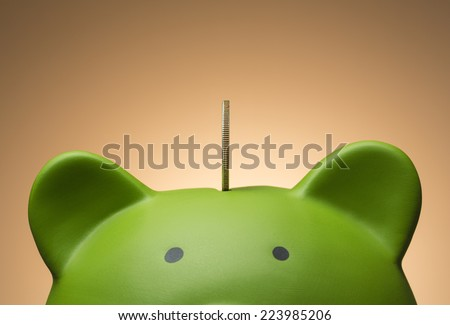 Close up show an edge view of a coin in the slot of a green piggy bank. - stock photo