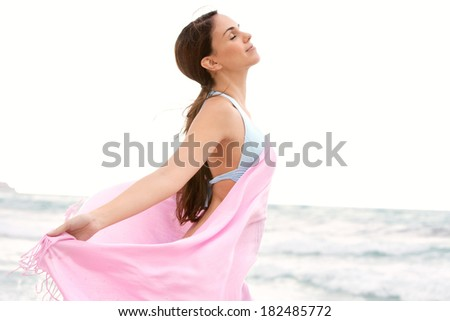 Close up side portrait of a beautiful young woman relaxing on a beach on holiday holding a pink fabric sarong around her body and floating in the breeze, breathing fresh air, lifestyle. - stock photo
