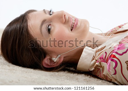 Close up side portrait of a young beautiful woman listening to music with her earphones while laying down on a furry carpet at home. - stock photo