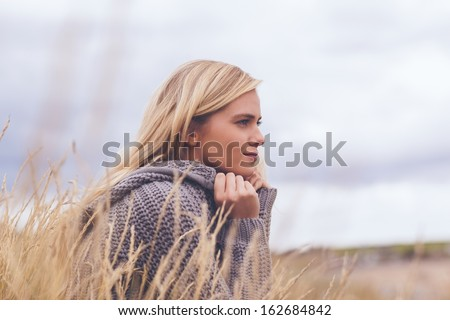 Close up side view of a cute thoughtful young woman lying on grass at beach - stock photo