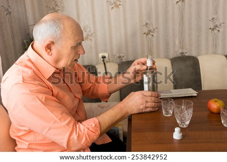 Close up Side View of a Serious Old Man Holding a Bottle of Vodka Wine on the Wooden Table - stock photo