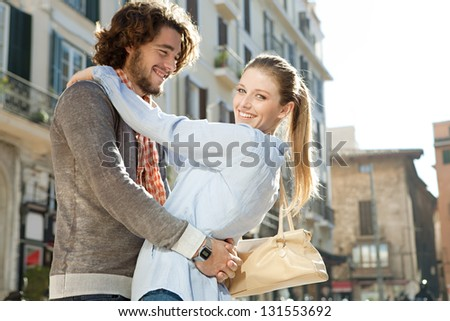 Close up side view of an attractive couple hugging and being playful while having fun on vacation, with the sun rays filtering through.