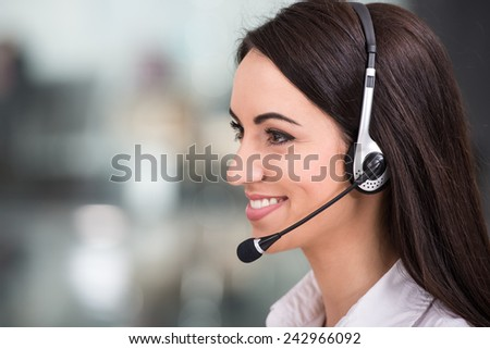 Close-up, side view of attractive young woman is working in a call center. - stock photo