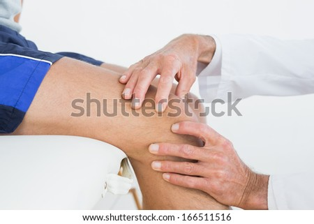 Close-up side view of hands examining patients knee at the medical office - stock photo