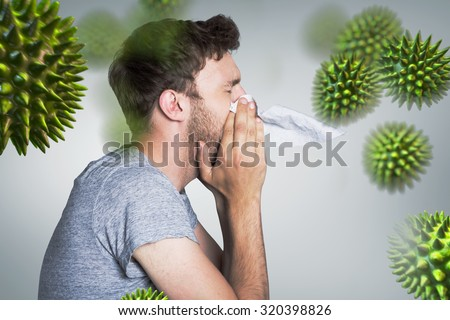 Close up side view of man blowing nose against grey vignette - stock photo