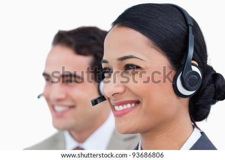 Close up side view of smiling call center agents against a white background - stock photo