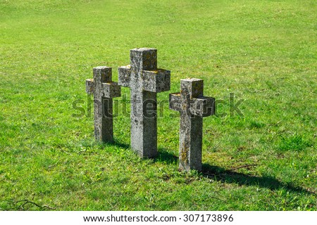 Close up side view of three stone cross signs in a meadow area, on green grass background. - stock photo