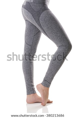 Close up side view of woman legs stretching the muscles of the foot in gray sports thermal underwear with pattern on white background.                           - stock photo