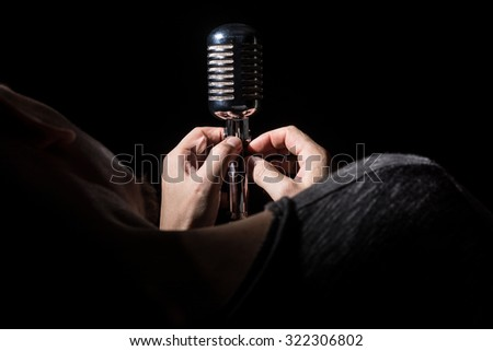 Close-up singer song prepares microphone sings a song. - stock photo
