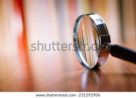 Close up Single Magnifying Glass with Black Handle, Leaning on the Wooden Table at the Office. - stock photo