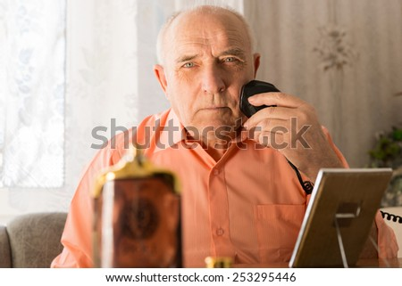 Close up Sitting Elderly Shaving his Beard Using Electric Razor with Mirror and Aftershave Bottle on the Table. Looking at the Camera. - stock photo