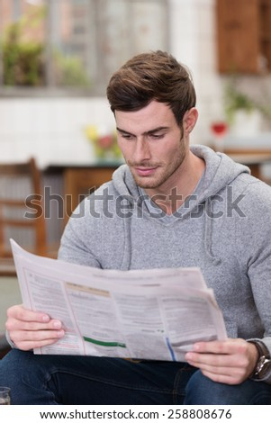 Close up Sitting Handsome Young Man in Gray Long Sleeve Shirt with Hood, Reading Newspaper Articles Seriously. - stock photo