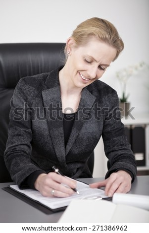 Close up Sitting Happy Businesswoman in Black Office Attire Writing on a Paper at her Desk. - stock photo