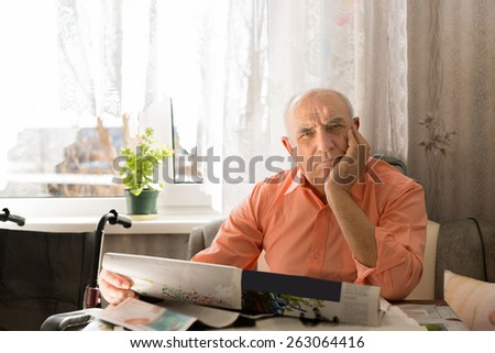 Close up Sitting Old Man Holding Newspaper While Looking at the Camera with One Hand on the Face. - stock photo