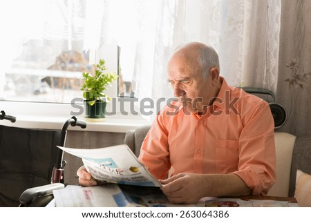 Close up Sitting Pensioner Reading News on Tabloid While Resting at the Living Area Near the Window. - stock photo