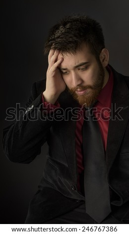 Close up Sitting Worried Goatee Man in Formal Suit, Putting his Hand on his Face. Captured on Gray Background - stock photo