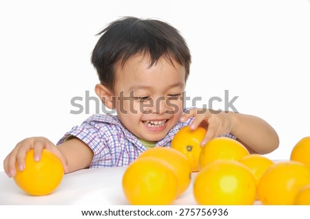 Close up Smile boy holding oranges - stock photo
