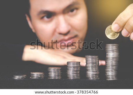 Close-up Smiling Asian Handsome Man Put Coins to Stack of Coins - stock photo