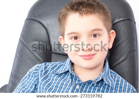 Close up Smiling Cute American Boy Sitting on a Black Office Chair, Looking at the Camera, on a White Background. - stock photo