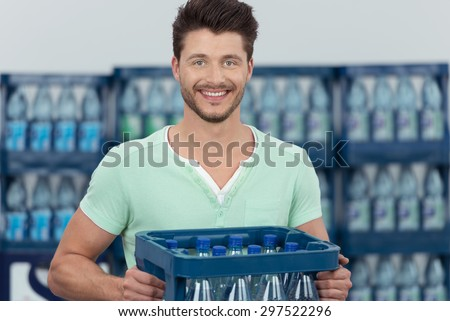 Close up Smiling Handsome Young Bearded Guy Carrying a Case of Bottled Water and Looking at the Camera. - stock photo
