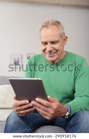 Close up Smiling Middle Aged Guy Looking at the Screen of his Tablet Computer on his Hand, While Sitting at the Couch in the Living Area. - stock photo