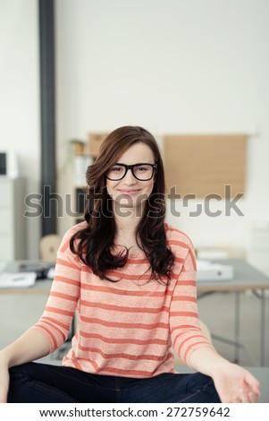 Close up Smiling Pretty Girl in Trendy Fashion Sitting in a Yoga Position While Looking at Camera - stock photo