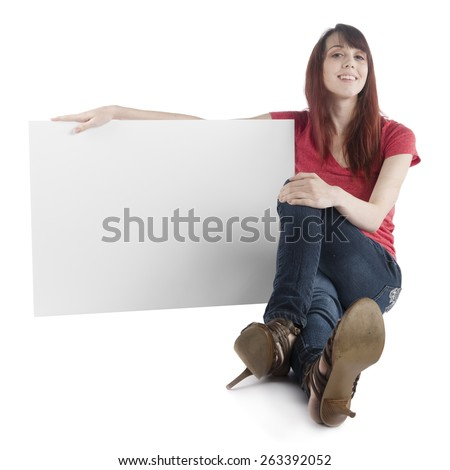 Close up Smiling Pretty Woman, Sitting on the Floor, Holding Empty White Cardboard While Looking at the Camera. Isolated on White, Emphasizing Copy Space.