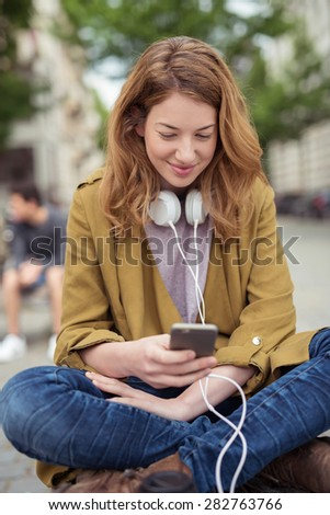 Close up Smiling Teen Blond Girl Sitting on the Bench with Legs Crossed, Browsing Something at her Mobile Phone. - stock photo